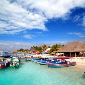 Zusehen ist der Bootshafen der Insel Mujeres mit vielen kleinen Fischerbooten. Im Hintergrund sind einige Restaurants zu sehen.