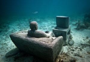 Zusehen ist das von Jason deCaires Taylor installierte Unterwassermuseum vor der Küste der Insel Mujeres. Ein Mann sitzt vor dem Fernseher.