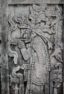 Zusehen ist ein Maya Stein Relief mit einem Maya Priester welcher an einer Pfeife raucht.