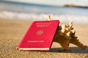 Deutscher Reisepass am Strand, angelehnt an eine große Muschel.