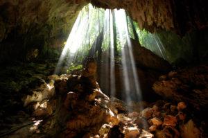 Eingang in die Cenote in Rio Secreto. Die Sonnenstrahlen fallen in die Cenote.