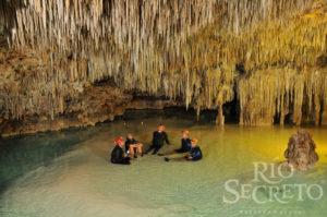 Die Stille in den Höhlen von Rio Secreto genießen. Eine Gruppe sitzt in der Höhle im seichten Wasser.